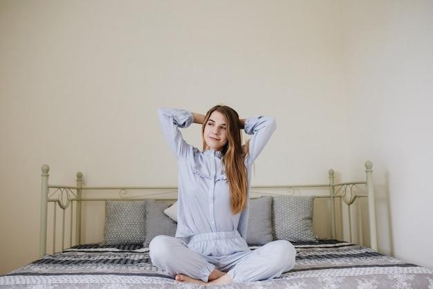 Девушка проснулась и сидит в пижаме на кровати в своей комнате. стильный серо-белый интерьер. девушка растягивается.