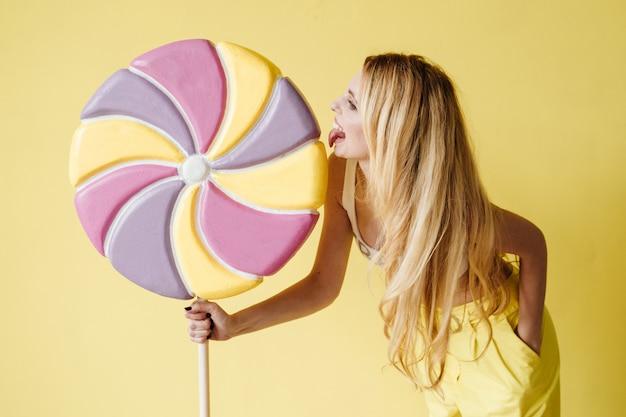 Портрет модной молодой блондинки, одетой в желтые штаны, кеды с большой конфеткой