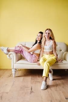 Две девушки, брюнетка и блондинка, в ярких брюках на светлом диване у стены желтой стены.