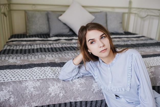 少女は目を覚まし、彼女の部屋のベッドの上の彼女のパジャマに座っています。スタイリッシュなグレーホワイトのインテリア。
