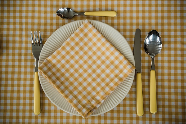 ピクニックセット。カトラリー、テーブルクロス、バスケット、スプーン、フォーク、ナイフ、グラス、ナプキン。ロマンチックなデート。家族の週末。黄色いセル。完璧な家族。水仙。テキストまたは写真のフレーム。