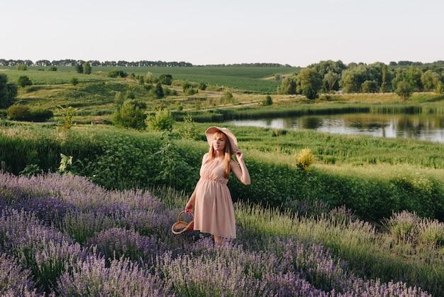Беременная девушка блондинка в бежевом платье и соломенной шляпе. лавандовое поле. в ожидании ребенка. идея фотосессии. прогулка на закате. будущая мама корзина цветов.