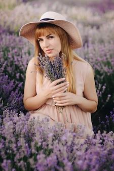 Беременная девушка блондинка в бежевом платье и соломенной шляпе. лавандовое поле. в ожидании ребенка. идея фотосессии. прогулка на закате. будущая мама портрет. букет цветов.