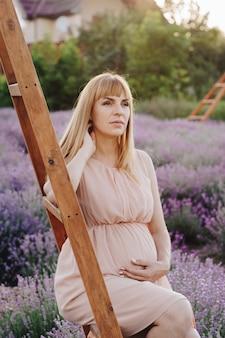 Беременная девушка блондинка в бежевом платье и соломенной шляпе. лавандовое поле. в ожидании ребенка. идея фотосессии. прогулка на закате. будущая мама сидит на стремянке.