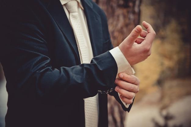 新郎はシャツのボタンを留めます。男の手。