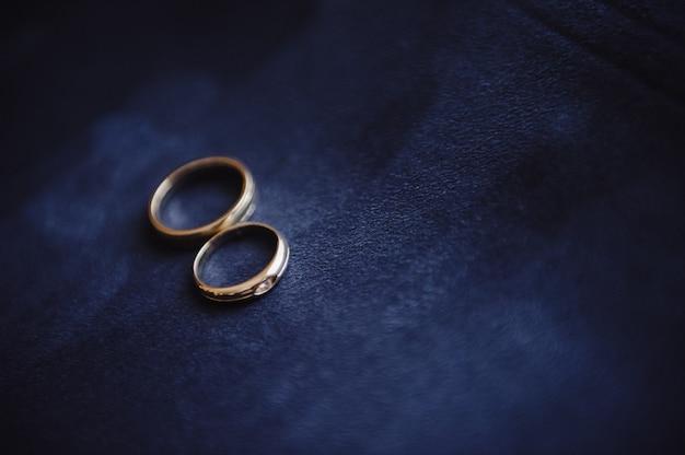 青いスエードの背景に結婚指輪。結婚式の詳細