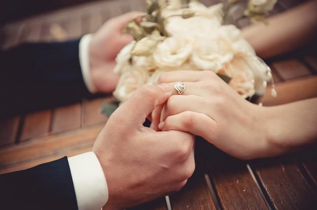 Свадебный букет из роз и молодоженов на деревянном фоне