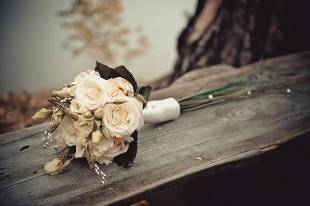 Свадебный букет из роз на деревянном фоне