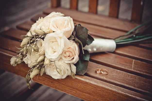 Свадебный букет из роз и колец на деревянном фоне