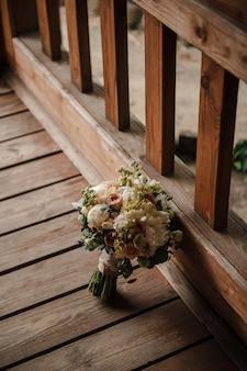 Букет невесты на деревянных фоне. букет из роз и пионов. свадьба.