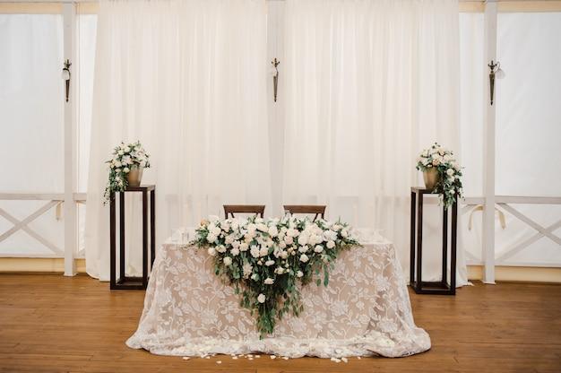 テントでの結婚式。ホールの装飾。白いテーブルクロス、美しい装飾、料理。美しい花の組成を持つ新郎新婦の幹部。白い花。古典的な結婚式。
