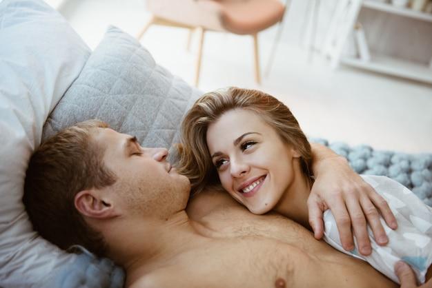 寝室のベッドの上の寝室のカップル。裸の胴体を持つ男のパジャマのブロンドの女の子。クリスマスの時期。