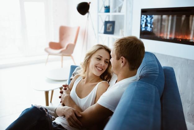 Парень и девушка обнимаются и целуются на синем диване. елка украшена. электронный камин. блондинка в белой футболке и джинсах.