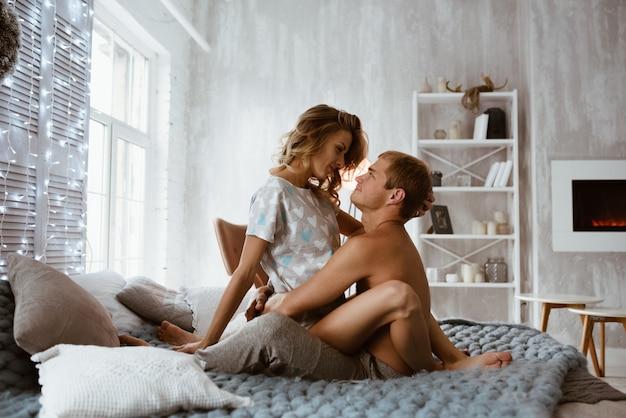 ベッドの上の寝室のカップル。裸の胴体を持つ男のパジャマのブロンドの女の子。クリスマスの時期。大きな交尾の毛布。