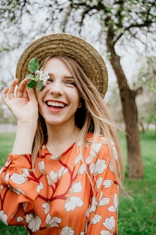 Молодая красивая блондинка женщина в цветущем саду. весенние деревья в цвету. оранжевое платье и соломенная шляпа.