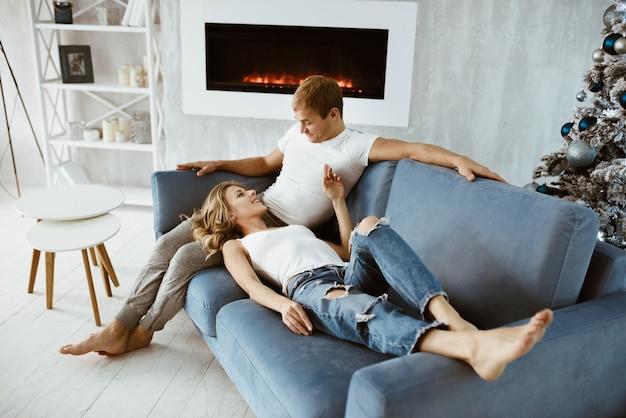 Парень и девушка обнимаются и целуются. елка украшена игрушками. электронный камин. блондинка в белой футболке и джинсах.