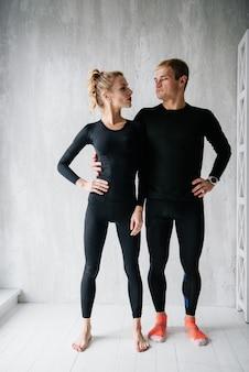 トラックスーツを着た男と女。黒のスポーツユニフォーム。男性と女性のアスリート。体をポンプアップ。トライアスロン。朝の運動。体のエクササイズのセット。ペアのクラス。自宅で一緒にトレーニング。