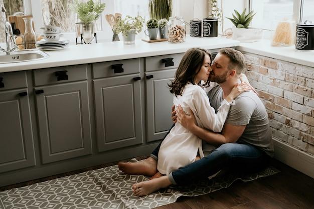 Девушка в белой рубашке и парень в серой футболке на кухне. целую и обнимаю.