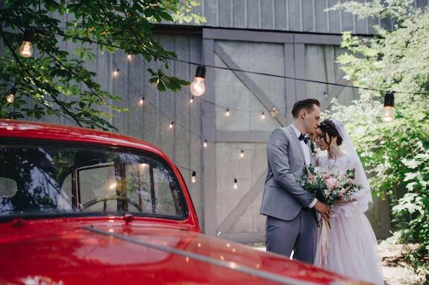 新郎新婦は赤い希少車の近くの庭を歩きます。森の中の結婚式。