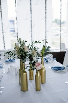 Подается на свадебный банкетный стол в сине-белом. свадебные украшения. голубая салфетка с цветком на белом фоне. золотые бутылки - это вазы для цветов.