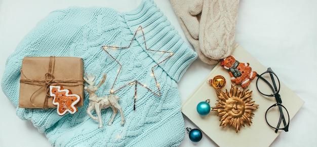 青いセーター、ニットミトン、クリスマスデコレーションとギフト