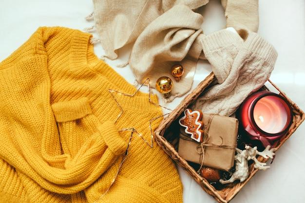 黄色いセーター、ニットのミトン、クリスマスの飾り、白い背景の上の贈り物