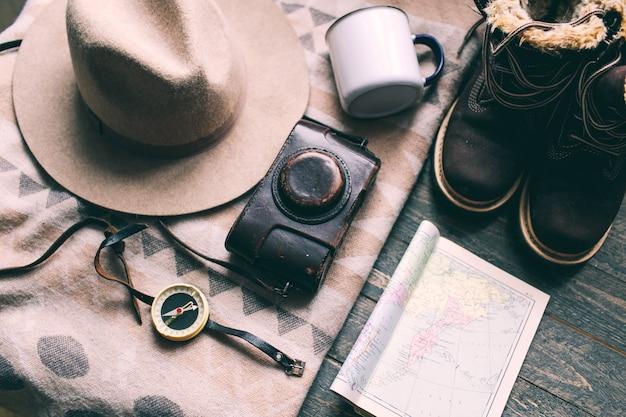 木製の床に山のものをハイキングブーツカメラ帽子マップコンパス