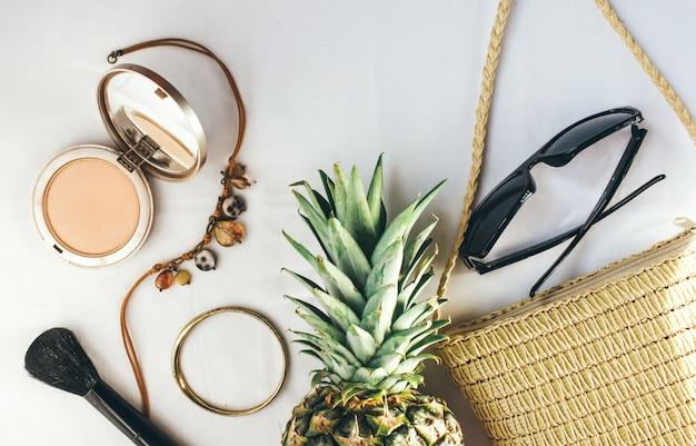 ウィッカーバッグパイナップルと化粧品は女性のための明るい背景の服装です。