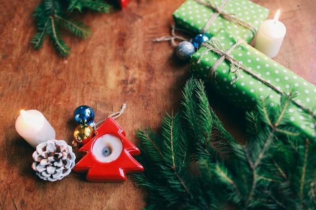 Новогодняя атмосфера, новогодний подарок и подставка для свечи рядом с елкой и елочными игрушками