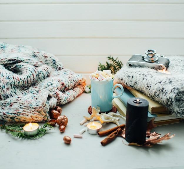 Кофе с зефиром в красивой чашке, рождественский декор и свечи хорошего настроения