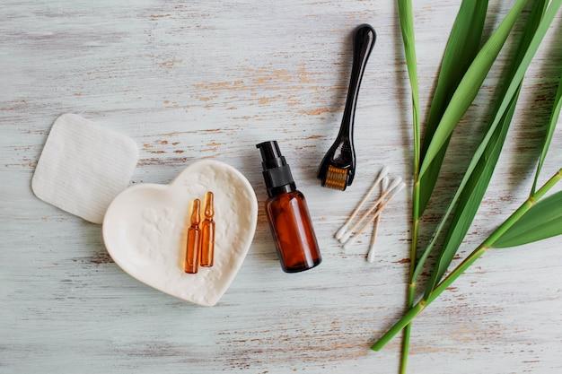 アンチエイジングフェイスクリームの横にあるダーマローラーと美容液美容産業医療用マイクロニードルセラピー用のクローズアップダーマローラー