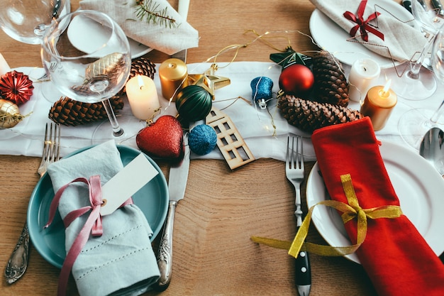 Стол подается на рождественский ужин в гостиной. крупным планом вид, сервировка стола, тарелки, филиал украшения, свечи и блестящие игрушки на фоне деревянный стол