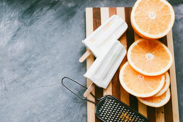 Домашнее мороженое с кокосом и апельсином апельсиновое мороженое лежит рядом с фруктами на светлом фоне