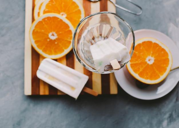 Мороженое кокосовое и апельсиновое апельсиновое мороженое лежит рядом с фруктами на светлом фоне