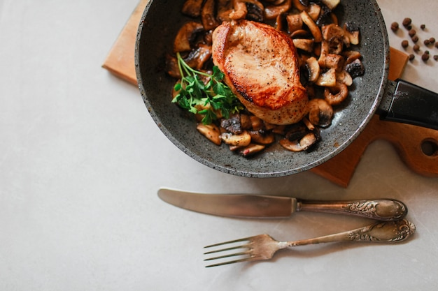 Курица с грибами на сковороде лежит на светлом фоне куриный обед рядом со старинными столовыми приборами