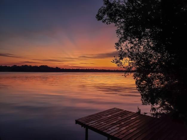 Закат на реке летом и деревянный пирс
