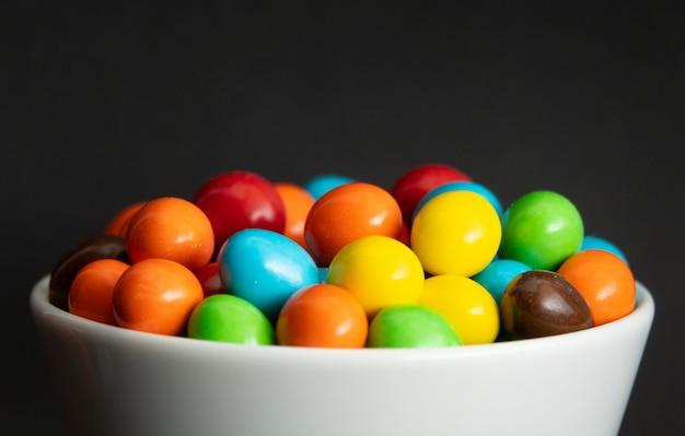 カラフルなチョコレートコーティングキャンディー、チョコレートの背景の山のクローズアップ