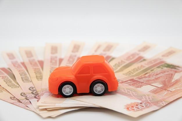 紙幣の背景にルーブルのおもちゃの車で車を買う。