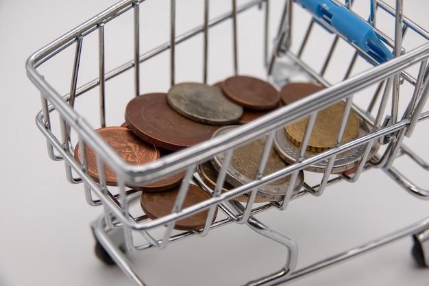 白い背景の上のユーロ硬貨でいっぱいショッピングカート
