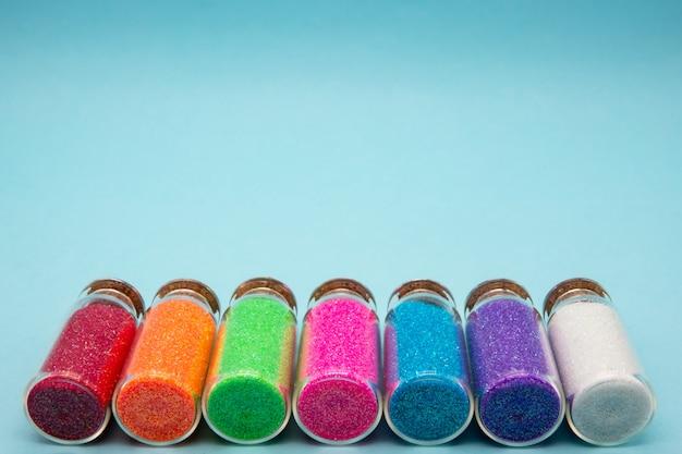 Мода концепция маленьких баночек с красочными конфетти на синей стене