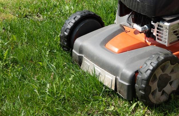 Человек движется с газонокосилкой, косит зеленую траву