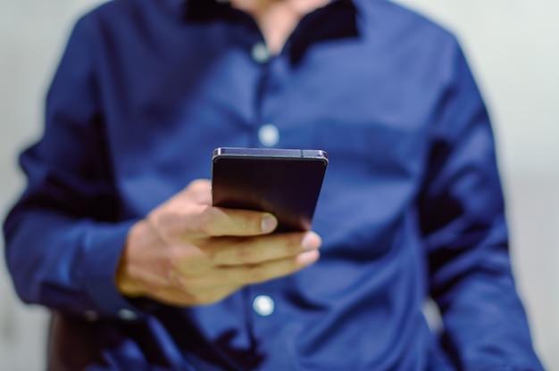 ビジネスマンはスマートフォンを使用してスマートフォンをプレイ