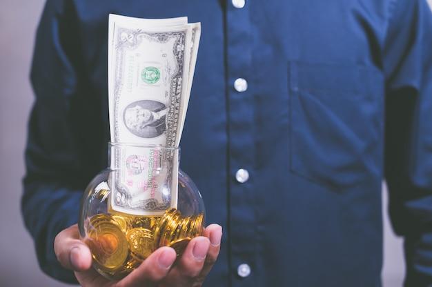 お金を持ち、利益を上げ、お金を節約するビジネスマンのアイデア。