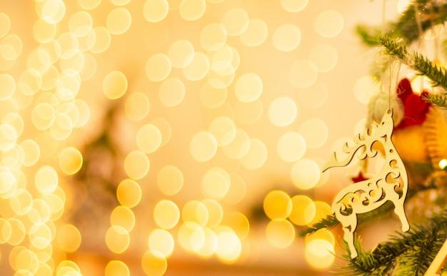 美しい明るい黄色のぼかしとクリスマスツリーの新年の鹿の装飾