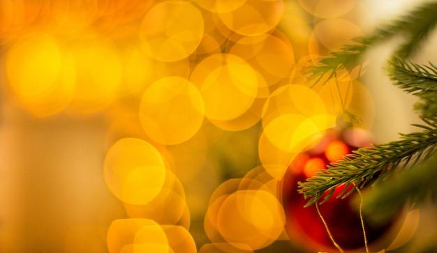 美しい明るい黄色のぼかしとクリスマスツリーの新年のボールの装飾