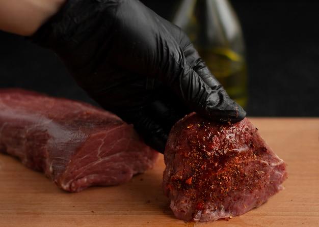 Рука в черной перчатке держит стейк из говядины со специями на деревянной доске