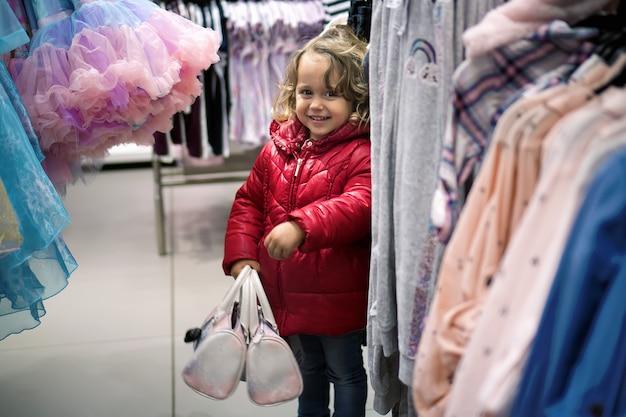 販売のための店で探している小さな女の子