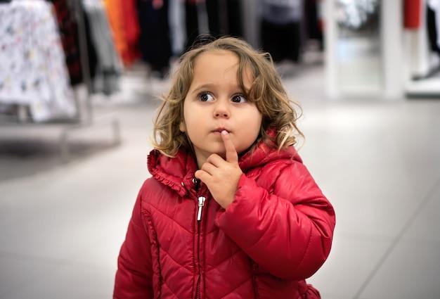 店で何を買うべきか考える小さな女の子