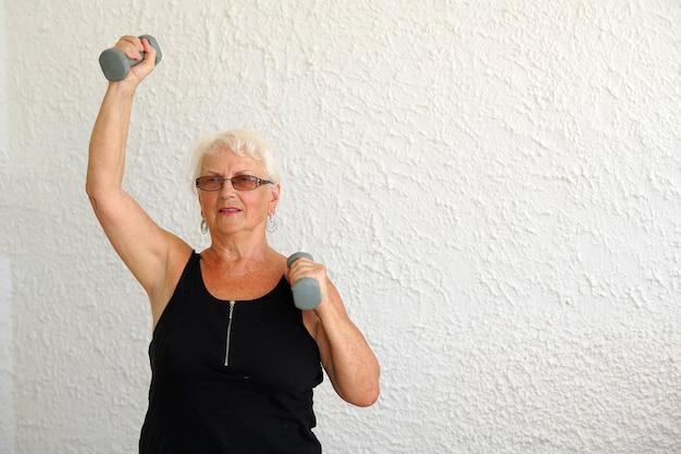 Пожилая женщина делает упражнения с гантелями