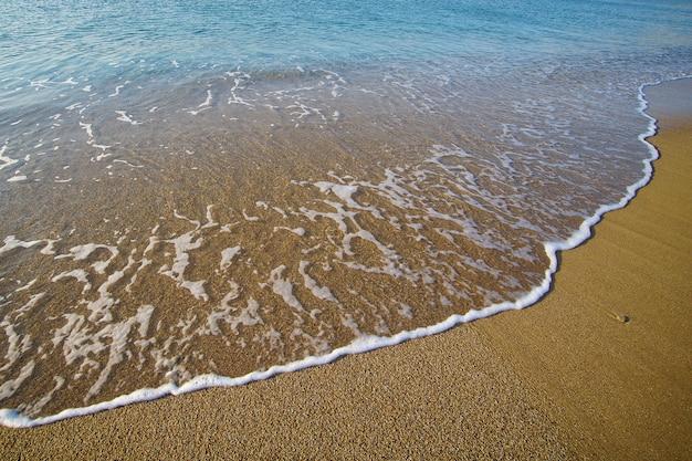 ミコノス島のリアビーチの黄金のユニークな砂の上に海によって描かれたグラフィック構成